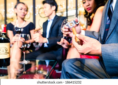 Man sitting with friends and cutting cigar