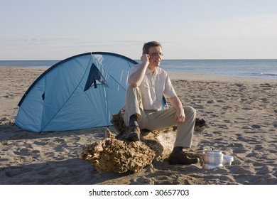 Man sitting in front of his tent on a beach while making a phone call