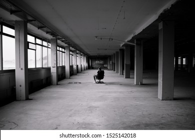 Man sitting in front of a large window in an empty hall of an abandoned building - black and white