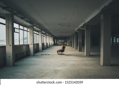 Man sitting in front of a large window in an empty hall of an abandoned building