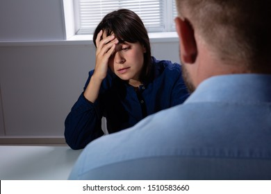 Man Sitting In Front Of Sad Worried Young Woman Suffering From Depression Looking Away