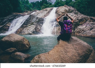 Man sitting in front waterfall in pahang,Malaysia.
