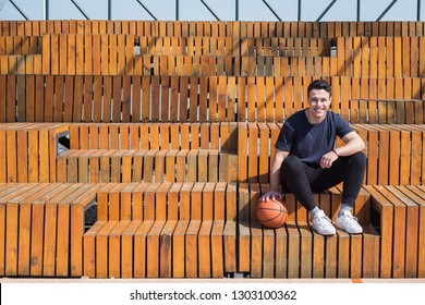 Man sitting in grandstand of basketball court