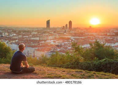 Man sitting in the grass and enjoying the sunrise over the city of Lyon, France.