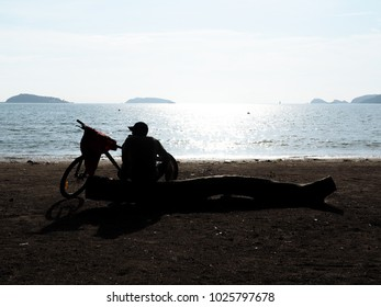 The man sitting with his bicycle  looking at the blue sea