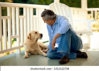 Man sitting with his dog on the verandah.