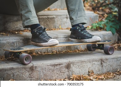 Man sitting with his feet on a longboard