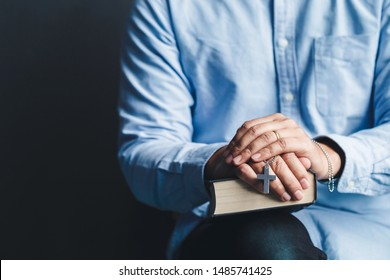 Man sitting holding bible and holds a cross in his hands.Christians and Bible study concept