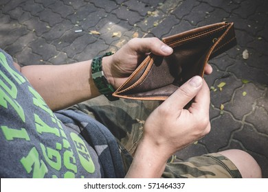 Man sitting and holding an empty wallet %3A top view
