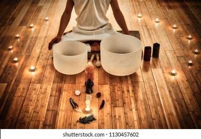 Man sitting in indian behind his two musical crystal bowls, with a display of sacred object and surrounded by candles