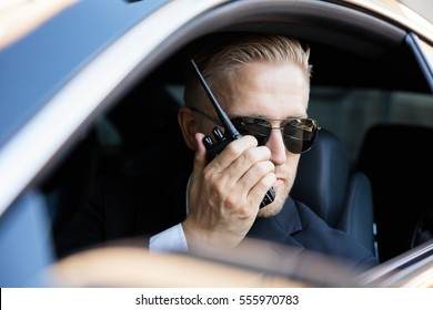 Man Sitting Inside Car Doing Surveillance Talking On Walkie Talkie