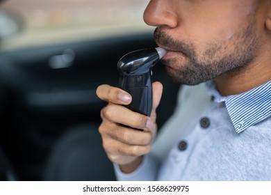Man Sitting Inside Car Taking Alcohol Test