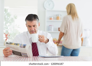 Man sitting at the kitchen table while reading a newspaper and holding a cup of coffee before work