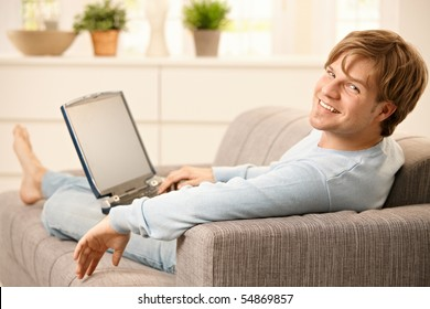 Man sitting with laptop computer on sofa  with feet up in living room, looking back at camera, smiling.