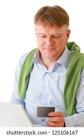 A man sitting with a laptop, holding a credit card