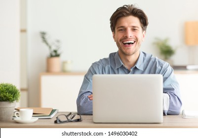 Man Sitting At Laptop And Laughing Looking At Camera Indoor. Empty Space For Text
