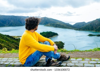 Man sitting looking at the Lake of Fire in San Miguel, Azores Islands
