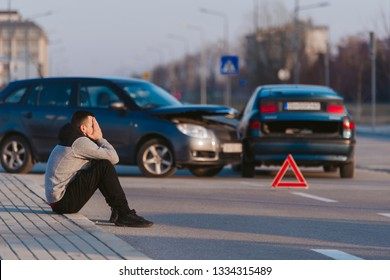 A man is sitting and looking nervous after two cars wrecking on the road