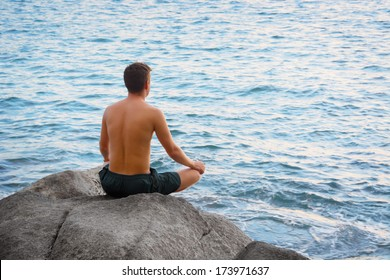 Man sitting in the lotus position and looking at the sea