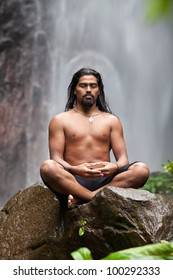 Man sitting in meditation on rock at waterfall in tropical rainforest