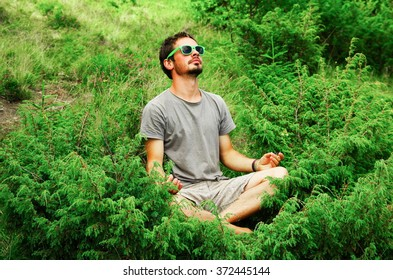 man sitting in meditation position surrounded by small green trees