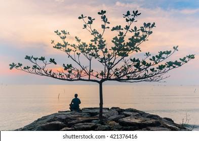 Man sitting meditation under a tree by the sea.