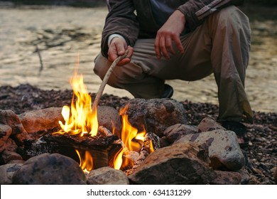 A man sitting near the campfire and enjoy the atmosphere.