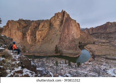 A man sitting near the edge of the cliff looking towards the volcanic rocks in Smith Rock State Park, Oregon