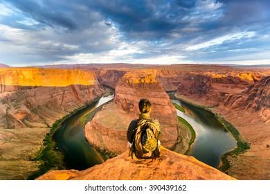 A man sitting near the edge at Horseshoe Bend, Arizona, USA