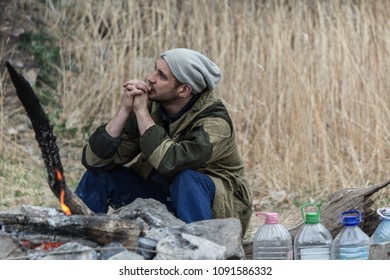 Man sitting near the fire on nature in early spring time (camping)