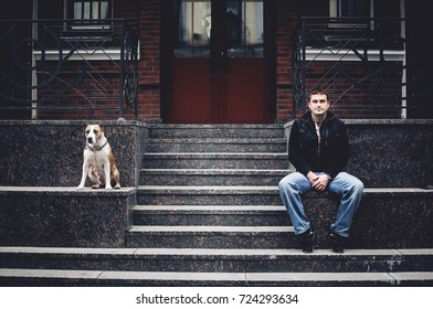 Man is sitting near the house with a dog