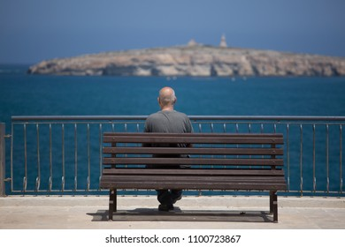 Man sitting near the ocean on the bench