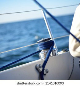 A man sitting next to a staysail winch on a sailboat on a clear day in an open sea