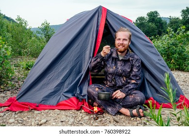 the man is sitting next to the tent and is preparing dinner
