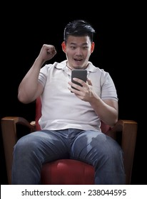 man sitting on arm chairs and watching to smart phone with exciting face