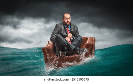 man sitting on an armchair floating on the water of the ocean. concept of crises and problems at work.