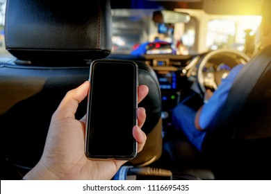 Man sitting on backseat taxi car and hand holding smartphone to use online application.