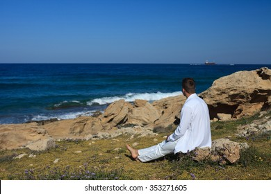 A man sitting on the beach and looking at sea. close-up