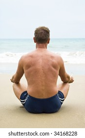 A man sitting on beach meditating.