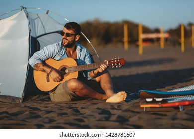 Man sitting on the beach singing and playing guitar