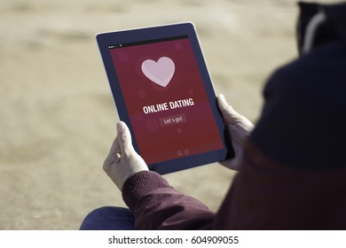 Man sitting on the beach and using online dating app with his tablet