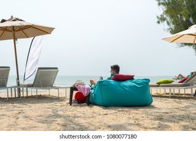 Man sitting on bean bags at the beach - Summer Time