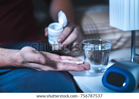 Man sitting on bed about to take sleeping pill or night medicine. Suffering from insomnia. Holding tablet and bottle in hand. Glass of water on nightstand in bedroom.