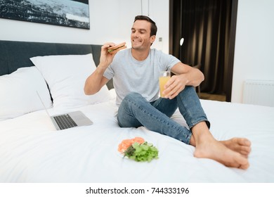 A man is sitting on the bed and having breakfast. In front of him stands an open gray laptop. He sits on a large white bed in the bedroom.