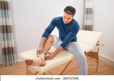 Man Sitting On Bed Typing Elastic Bandage To His Foot