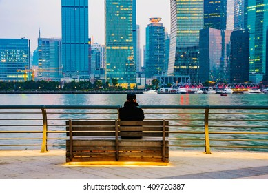 man sitting on a bench on The Bund looking at Shanghai financial district
