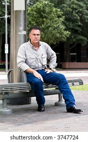 A man sitting on a bench at a downtown bus stop.