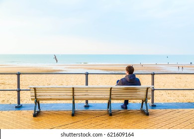 The man is sitting on the bench, the embankment of Oostende, Belgium