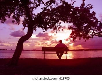 Man sitting on a bench enjoying sunset on the lake