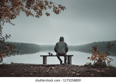 A man is sitting on a bench and looking at the lake. Back view. Also a coffee maker and a mug on the bench. Foggy morning. autumn theme